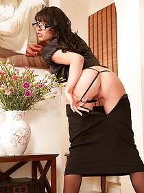 Glasses-wearing brunette in black stockings showing off on camera